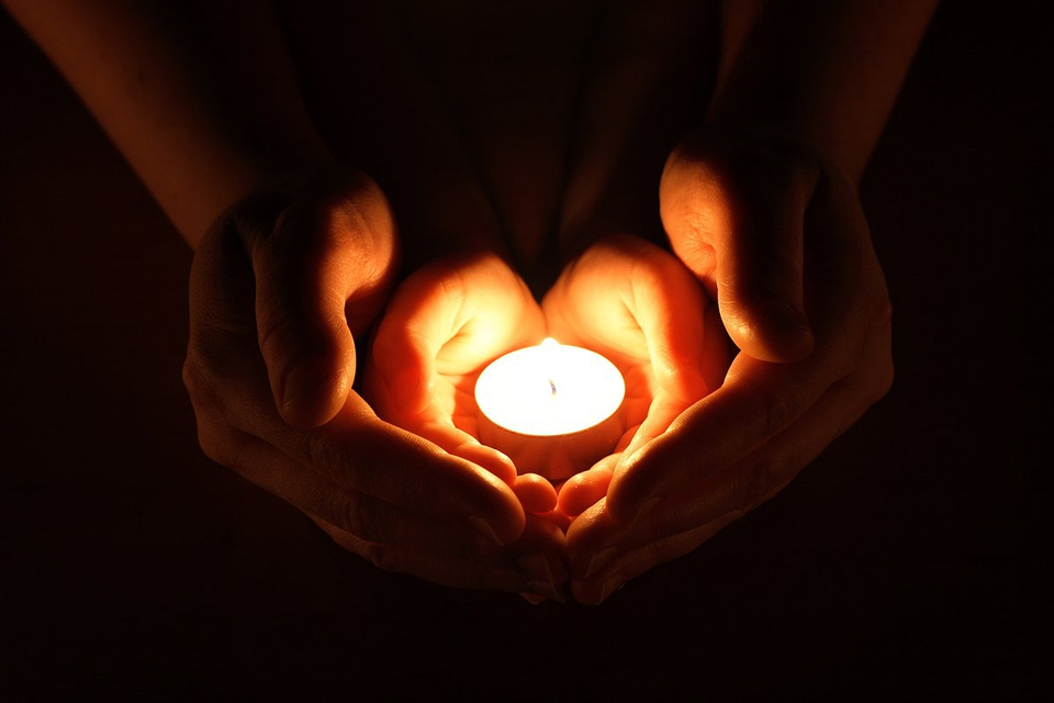 Hands held in prayer in the light of a candle